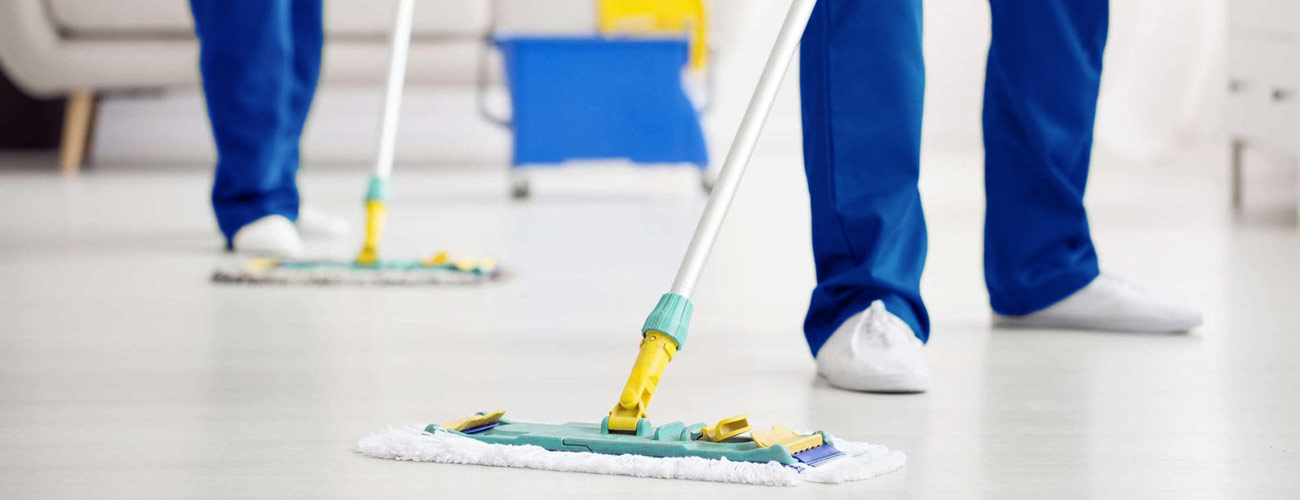 two professional plumbers cleaning and mopping floor after water flooding