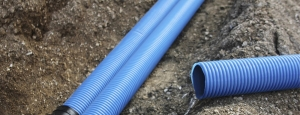 blue water pipes resting on dirt to be used for transporting water