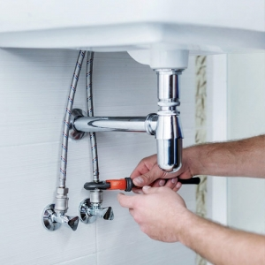 washroom water pipes being fixed by plumber under sink with wrench