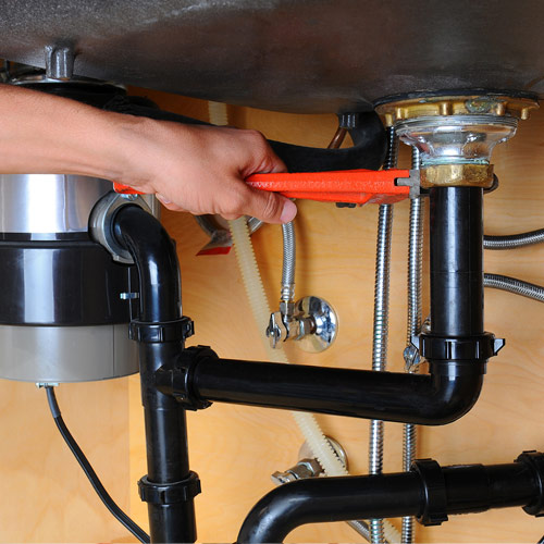 plumber with orange wrench fixing black pipe under a sink