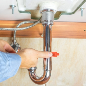 plumber fixing washroom sink pipe with wrench