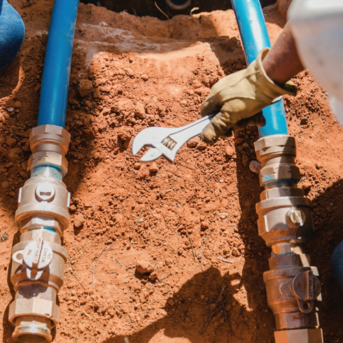 plumber repairing blue water pipes on dirt underground