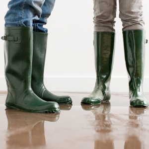 two people with gum boots standing in brown water that's over flowed