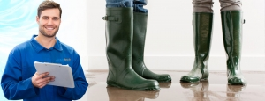 two people with gum boots standing in brown water that's over flowed banner