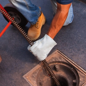 plumber with gloves inserting drain snake into ground large drain